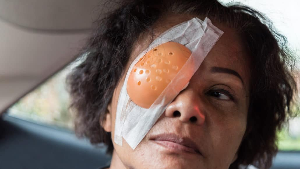 Patient asian elder women 60s with black hair and wrinkled on face show her eyes with eye pad and eye shield after cornea surgery (lasik) by ophthalmologist in the hospital.